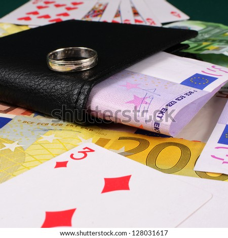 Wallet with money and a ring as a stake in gambling. Risk it all on gambling.
