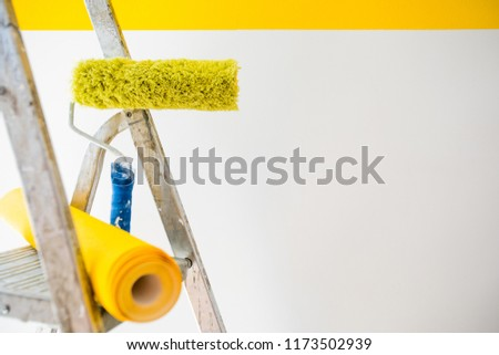 wallpaper and ladder, wallpapering  yellow color, gluing wallpapers on the wall, сoncept of repair home, instruments for a renovation #1173502939