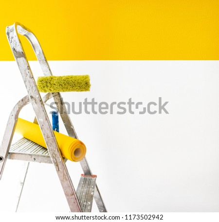 wallpaper and ladder, wallpapering  yellow color, gluing wallpapers on the wall, сoncept of repair home, instruments for a renovation #1173502942