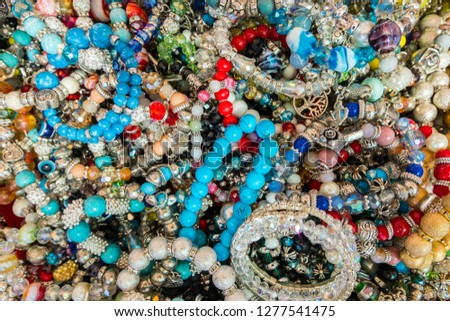 Wallpaper background of stylish bracelets made with colorful stones. Fake jewelery.