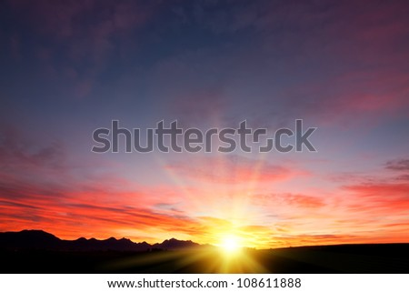 wallpaper background of sun filtered cloudscape morning sunrise over silhouetted mountains