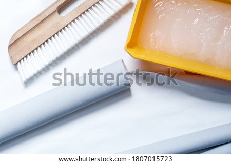 Wallpaper, brush for application and wallpaper glue. Close-up tools for wallpapering. Stockfoto ©