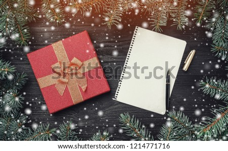 Wallpaper of winter holidays on black wooden background. Xmas card with light and snow effect. Letter for Santa Claus, intro frame of fir branches and red gift. Top view #1214771716