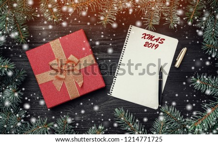Wallpaper of winter holidays on black wooden background. Xmas greeting card with light and snow effect. Letter for Santa Claus, intro frame of fir branches and red gift. Top view #1214771725