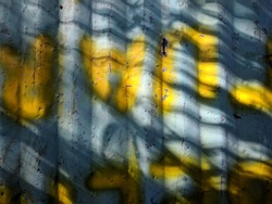Walls made of zinc with yellow graffiti were photographed in the morning