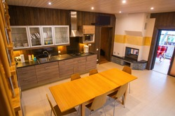 Walls of house are finished with wood. Large kitchen-dining room in cottage. Interior of room is made of wood. Concept - building material for home decoration. Large wood table in dining room.