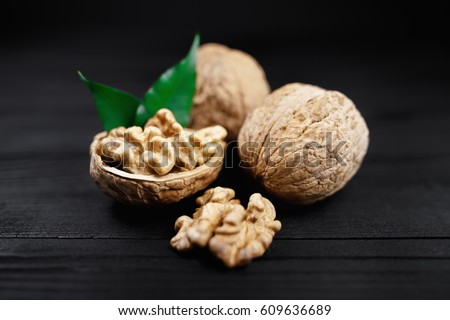 Walnut and walnut kernels and whole walnuts on rustic black wooden background