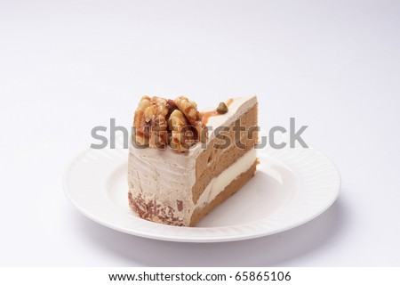 Walnut cake on the white plate with a cup of coffee