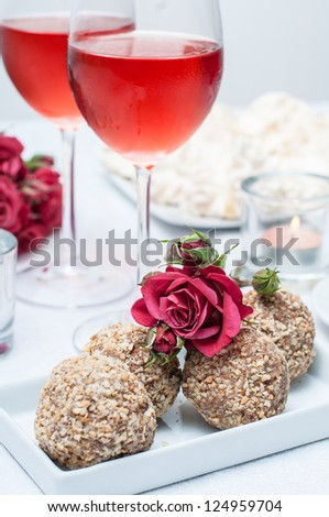 Walnut-chocolate cakes, flowers and rose wine in glasses on a festive table