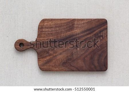 Walnut handmade wood cutting board on the linen
