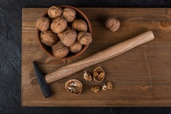 Walnut in a bowl and hammer on a wooden board