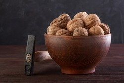 Walnut in pottery and hammer on a wooden table