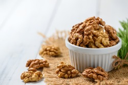Walnut in white cup on wood background. healthy nuts concept. Walnuts are an excellent source of antioxidants and including LDL cholesterol, which promotes atherosclerosis.