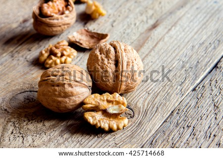 Walnut kernels and whole walnuts on rustic old wooden table with copy space