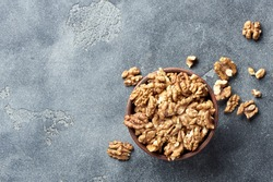 Walnut kernels on gray background with copy space. Nuts in clay bowl. Top view.