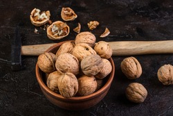 Walnut with hammer against the background of concrete