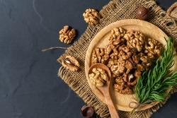 Walnuts and rosemary leaf in wood plate  on black table background. healthy nuts concept. Walnuts are an excellent source of antioxidants and including LDL cholesterol, which promotes atherosclerosis.