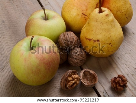 Walnuts, apples and pears on the old wooden table