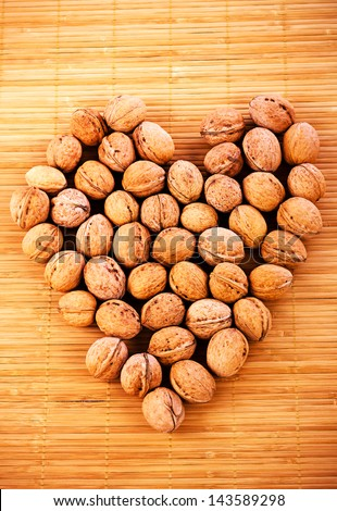 Walnuts forming hearth shape on wood background textures