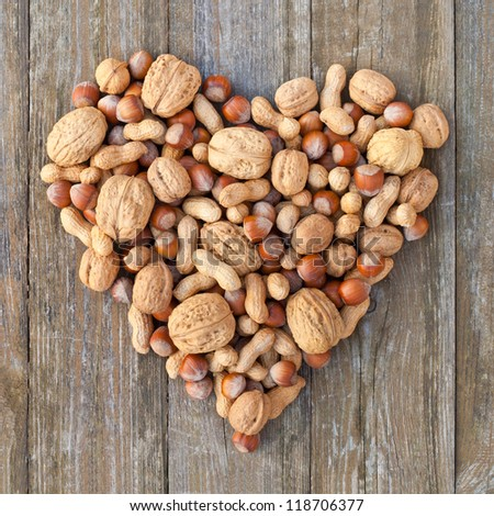 walnuts, hazelnuts and peanuts on wooden background/nuts/heart