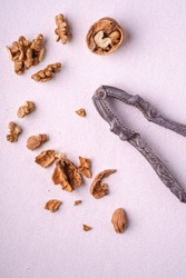 Walnuts heap food with half peeled nut, cracked nutshell, near to vintage nutcracker on white background, top view, healthy food concept