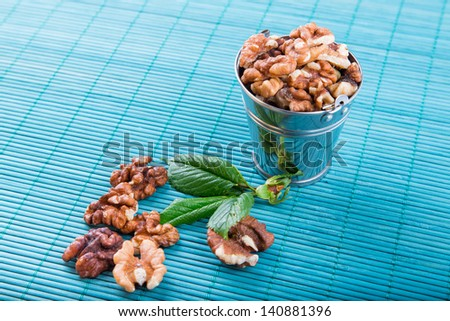 Walnuts in a backet scattered over blue bamboo overlay
