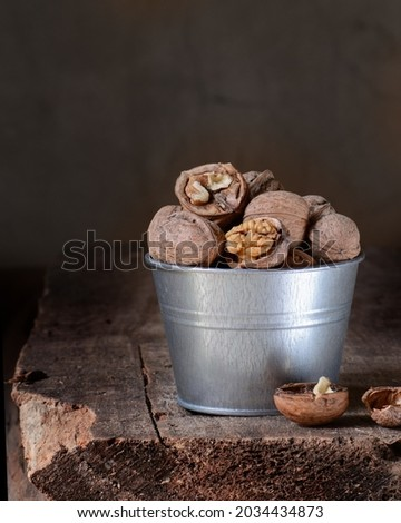 Walnuts in a metal pot stands on an old wooden board. Rustic, moody and dark style.  Blurred background. Autumn background Foto stock ©