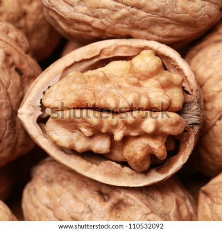 Walnuts in shells, one upon the other, one nut is open