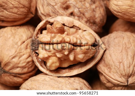 Walnuts in shells, one upon the other, one nut open