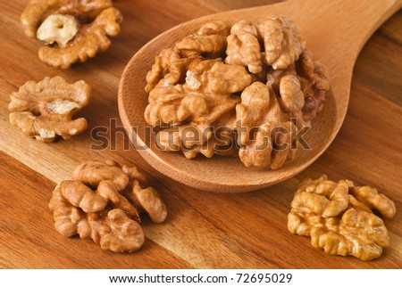 Walnuts in spoon on wooden background
