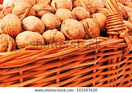 Walnuts in wicker basket on white background