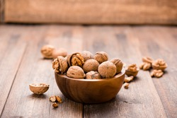 Walnuts in wooden bowl on table. Nuts.