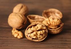 Walnuts kernels on dark desk with color background, Whole walnut in wood vintage bowl