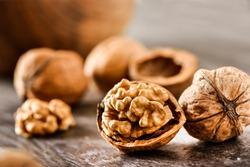 Walnuts kernels on dark desk with color background, Whole walnut in wood vintage bowl.