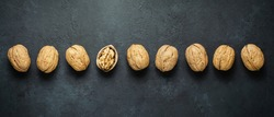 Walnuts on a dark concrete background. Nuts are a source of vegetable protein and vitamins. Flat top view, copy space.