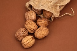 walnuts spilled on brown background