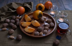 walnuts, tea drink, whole and chopped persimmons on a wooden tray, a candle is burning nearby and decorations on a green background