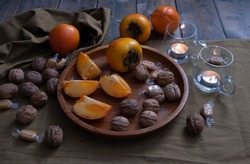 walnuts, tea drink, whole and sliced persimmons and caramel, a candle is burning nearby and decorations on a green background