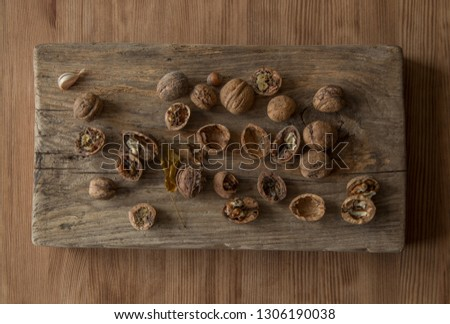 Walnuts, whole, broken, halves, acorn, garlic clove, yellow leaf, which are on the old wooden cutting board, which lies on the new wooden table.