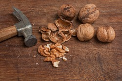 Walnuts with a hammer on a wooden board