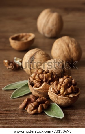 Walnuts with leaf on a wooden table.