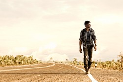 Wanderer or loner walking down an empty road and hot. Road hitch-hiking.
