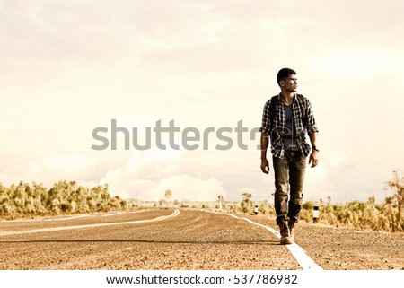 Shutterstock Wanderer or loner walking down an empty road and hot. Road hitch-hiking.