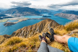 Wanderlust adventure and hiking travel vacation concept with hikers hiking boots close up. Hiker couple tramping up famous hike to Roys Peak on South Island, New Zealand. Couple resting and relaxing.