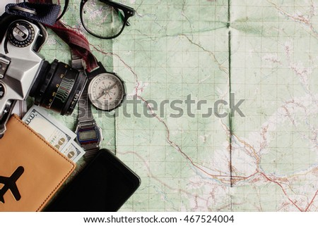 wanderlust and adventure concept, old compass phone photo camera glasses passport and money lying on map, top view, space for text, vintage toned image