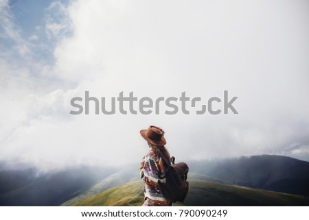 wanderlust and travel concept. girl traveler in hat with backpack looking at clouds in mountains. stylish hipster woman exploring on top of mountain. space for text. atmospheric moment