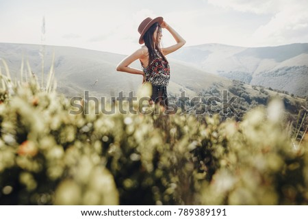 wanderlust and travel concept. stylish traveler woman in hat looking at mountains. hipster girl traveling on top of mountain, looking in front. space for text. atmospheric moment