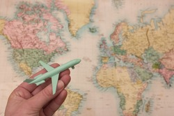 Wanderlust travel concept with hand holding airplane and blurred map background