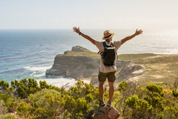 Wanderlust Traveler guy posing on stone at Cape of Good Hope, South Africa. Man in straw hat enjoying breathtaking landscape nature view on sea coast. Summer holiday vacation relax time at seaside.
