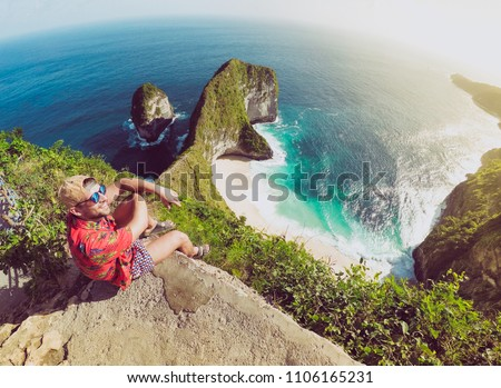 Wanderlust Young Man is Sitting on Cliff Rock at Kelingking Beach in Nusa Penida Indonesia Bali and Enjoying Amazing View. Concept of Nature Landscape Background with Traveler Guy Exploring Island. #1106165231